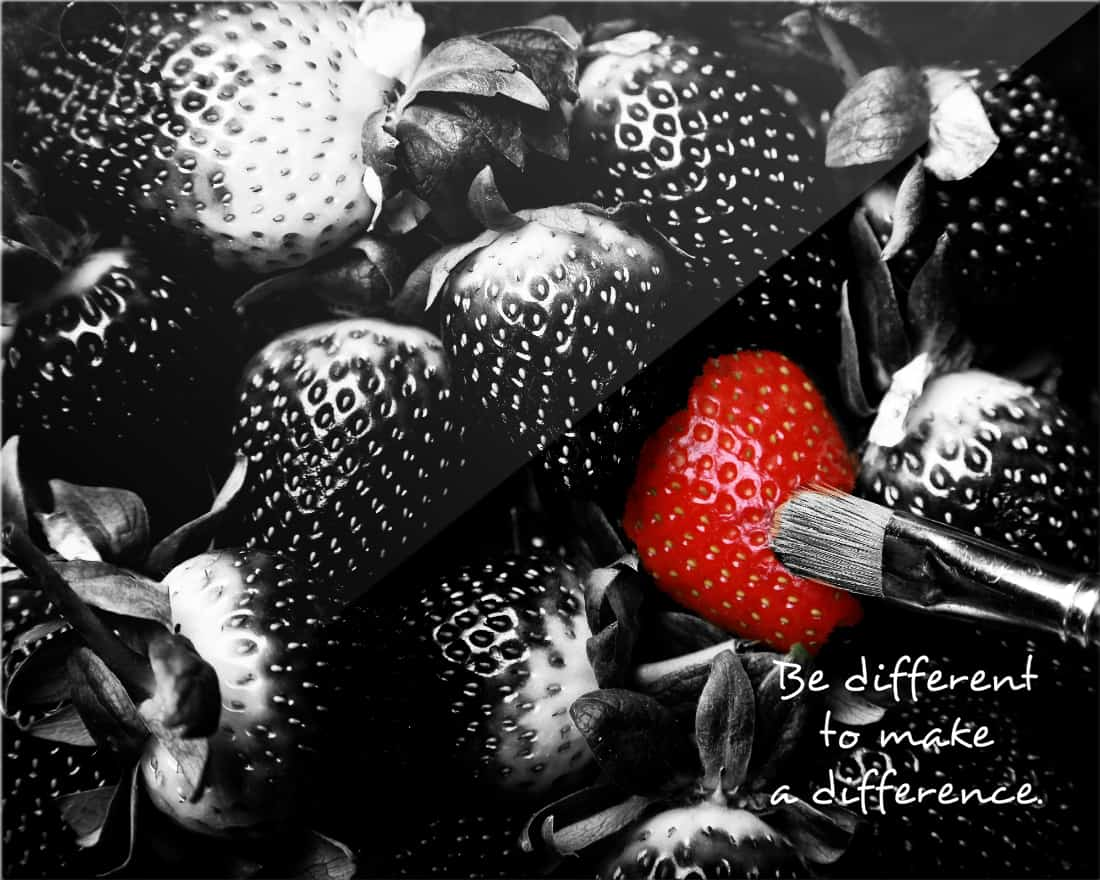 A black & white image of strawberries where a single red one stands out from the rest