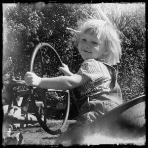 Toddler at the wheel of an antique tractor