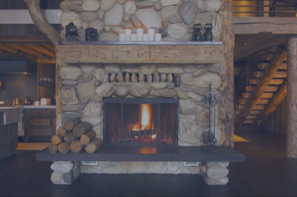 Central rustic fireplace in log cabin